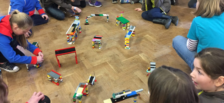 Guides, brownies and rangers gathered round different model bridges made of Lego