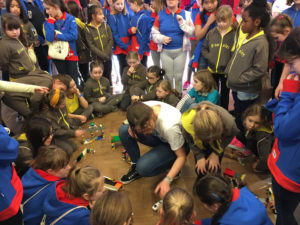 Guides, brownies and rangers gathered round different model bridges made of Lego. A woman sits in the middle of the group testing the bridges with a toy car