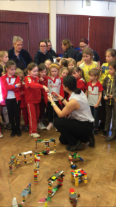 Brownies and Rainbows gathered round different model bridges made of Lego. A woman sits in the middle of the group and a Rainbow selects a toy car for the woman to test the bridge with